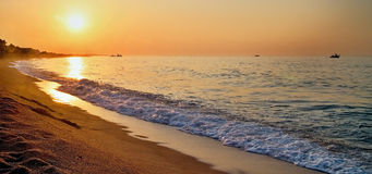 The rays of the rising sun over the Mediterranean Sea with a muddy background in Malgrat de Mar, Spain. Sun and sand, Mediterranean sea with sea waves, Sunrise Stock Photography