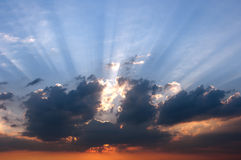 The rays of the setting sun behind the clouds. And blue sky Stock Images