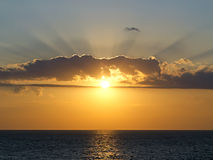 Rays of the setting sun breaks through the clouds. Over the sea stock image