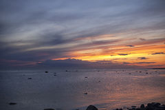 The rays of the setting sun over the sea. Sunset in pink, yellow and blue colors of the sea Stock Photography