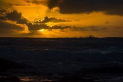 The setting sun sends out rays from behind the clouds over breaking surf Stock Image