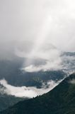 Rays struggle through the fog in mountains Royalty Free Stock Photo
