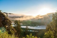 Rays of sun above mountain river. In the morning Stock Photos