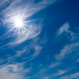Rays of sun on blue sky. Rays of sun on bright blue sky with fluffy clouds royalty free stock photography
