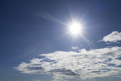 Rays of the sun in the blue sky and white clouds Stock Photo