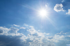 Rays of the sun in the blue sky and white clouds. Royalty Free Stock Images