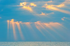 Rays of the sun breaking through the clouds over the sea Stock Photos