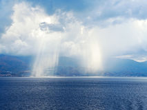 Rays of sun breaking through clouds in sea Royalty Free Stock Image