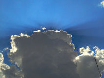 Rays of the sun breaking through the dark clouds on the blue sky background Royalty Free Stock Photo