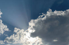 Rays from the sun breaking trhough the dark storm clouds filling. The blue sky Stock Photography