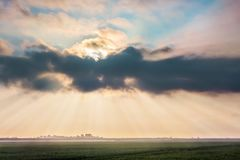 Rays of sun browsing through a dark cloud over wheat field dur. Ing sunrise. Summer landscape with a thunderstorm cloud royalty free stock photo