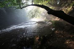 The sun`s rays illuminate the dark gorge royalty free stock image