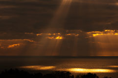 The rays of the Sun illuminate the surface of the. The Sun's rays of the morning sun sunlight Shimmers through clouds highlight the spots on the surface of sea Stock Photos