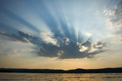 Rays of sun light breaking through from behind the clouds with n. An optical phenomenon created by sun rays bursting from a cloud and forming shadows on the sky Royalty Free Stock Photo