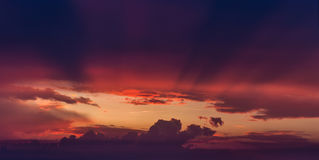 Rays of sun light on purple storm clouds Royalty Free Stock Images