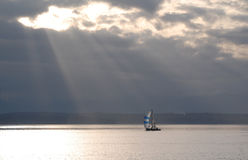 Rays of sun on a lone sailboat Royalty Free Stock Image