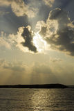 Rays of sun over sea water. Rays of sun shining through the clouds ,sunset over sea water Stock Image