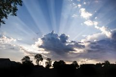 Rays of  sun penetrate through  cloud. Landscape with silhouette. S of trees and  large cloud with rays of  sun. Symbol of  Divine Light Royalty Free Stock Photos