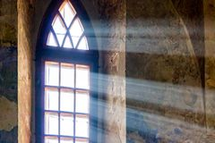 The rays of the sun penetrate through the window of the ancient. Church. Light overcomes the darkness royalty free stock photography