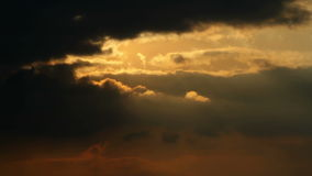 Rays of Sun Shine through Dark clouds after Rainfall. Static medium wide low angle shot of rain clouds filling a yellow and orange sunset twilight evening sky stock video footage