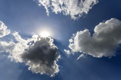 Rays of sun shining through white puffy clouds and blue sky.  Stock Photo