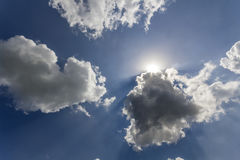 Rays of sun shining through white puffy clouds and blue sky Stock Photography