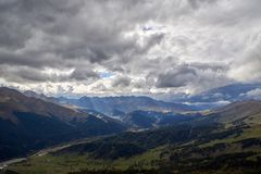 Rays of the sun through the stormy sky over a mountain valley stock photo