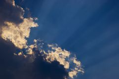 Rays of sunlight. Light streaks behind cloud in blue sky Stock Photography