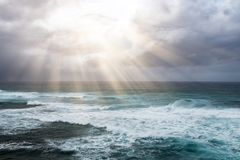 Rays of sunlight break through storm clouds above the open ocean Stock Image