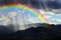 Rays of Sunlight on Peaceful Mountains and Rainbow Stock Photo