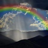 Rays of Sunlight on Peaceful Mountains and Rainbow Stock Photos