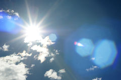 Rays of sunshine on a blue sky. With a smattering of white clouds Stock Images