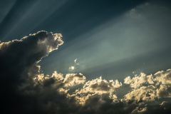 Rays of sunshine breaks through the dark clouds Royalty Free Stock Image