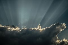 Rays of sunshine breaks through the dark clouds Stock Photos