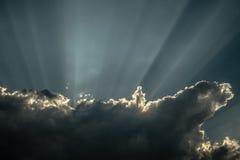Rays of sunshine breaks through the dark clouds stock photos