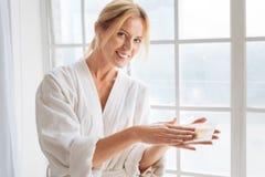 Rayures de chauffage de cire de femme avec du charme dans des ses mains Image stock
