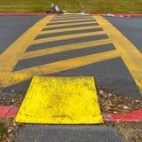 Rayures diagonales jaunes de cadre carré entre les lignes parallèles peintes sur une route pavée photos stock