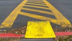 Rayures diagonales jaunes de panorama entre les lignes parallèles peintes sur une route pavée photo stock