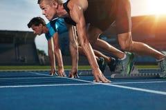 Raza corriente del atleta apto en pista del atletismo en un día soleado Imagen de archivo libre de regalías