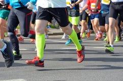 Raza corriente del maratón, muchos pies de los corredores en el camino, deporte, aptitud y forma de vida sana Imágenes de archivo libres de regalías