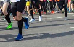 Raza corriente del maratón, pies de los corredores en el camino Foto de archivo