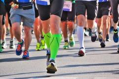 Raza corriente del maratón, pies de los corredores en el camino Foto de archivo libre de regalías