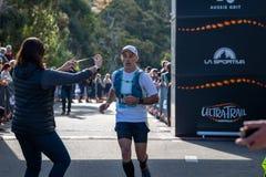 Raza de Australia UTA11 del Ultra-rastro Corredor Tim Lovettat la meta que recibe la medalla de la participación fotografía de archivo