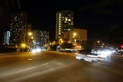 Raza de coches a lo largo del bulevar de Kapiolani en la noche Fotos de archivo libres de regalías