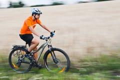 Raza de la bici cerca del campo Foto de archivo