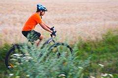 Raza de la bici cerca del campo Fotografía de archivo
