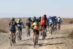 Raza de la bici en el camino del desierto Fotos de archivo