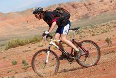 Raza de la bici en montañas del desierto Foto de archivo