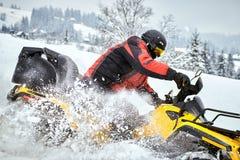 Raza del invierno en un ATV en nieve en el bosque Foto de archivo