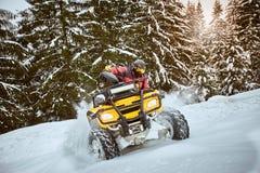 Raza del invierno en un ATV en nieve en el bosque Imagen de archivo libre de regalías